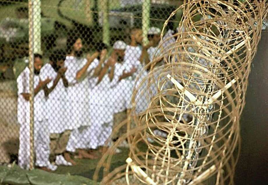 FILE - In this May 14, 2009 file photo, reviewed by the U.S. military, Guantanamo detainees pray before dawn near a fence of razor-wire, inside Camp 4 detention facility at Guantanamo Bay U.S. Naval Base, Cuba. The Obama administration is looking at creating a courtroom-within-a-prison complex in the U.S. to house suspected terrorists, combining military and civilian detention facilities at a single maximum-security prison. Several senior U.S. officials said the administration is eyeing a soon-to-be-shuttered state maximum security prison in Michigan and the 134-year-old military penitentiary at Fort Leavenworth, Kan., as possible locations for a heavily guarded site to hold the 229 suspected al-Qaida, Taliban and foreign fighters now jailed at the Guantanamo Bay detention camp in Cuba.  (AP Photo/Brennan Linsley, File) Photo: Brennan Linsley, AP