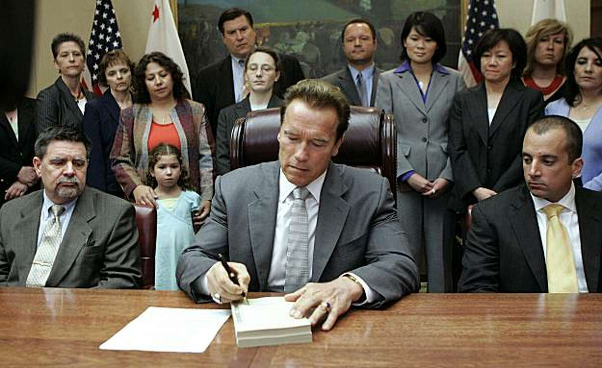 Gov. Arnold Schwarzenegger signs the $85 billion revised state budget as Finance Director Mike Genest, seated left, and Legislative Secretary Michael Prosio, seated right, look on during ceremonies at the Capitol in Sacramento, Calif., Tuesday, July 28, 2009. (AP Photo/Rich Pedroncelli)
