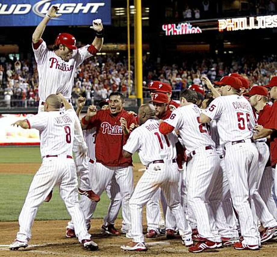 Philadelphia Phillies' Jayson Werth, top left, celebrates with his teammates after he hit a three-run home run against the Chicago Cubs in the 13th inning of a baseball game Tuesday, July 21, 2009, in Philadelphia. The Phillies won 4-1. (AP Photo/H. Rumph Jr.) Photo: H. Rumph Jr, AP