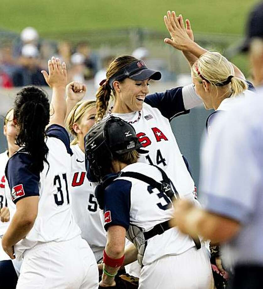 United States starting pitcher Monica Abbott (14) exchanges high-fives with teammates, including Jennie Finch, right, after delivering three strike outs in the first inning against Australia in the World Cup of Softball championship game in Oklahoma City, Monday, July 20, 2009. (AP Photo/Nati Harnik) Photo: Nati Harnik, AP