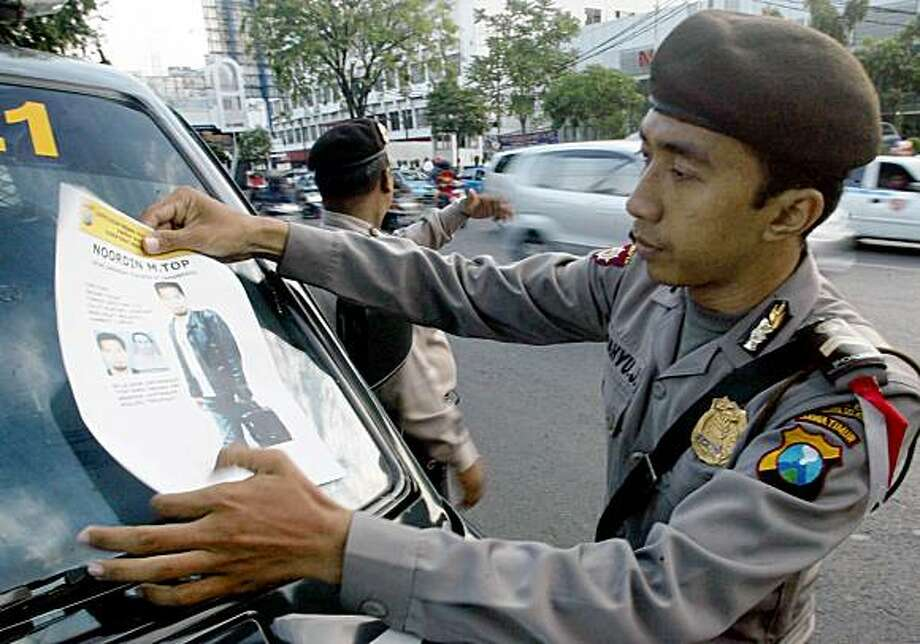 An Indonesian police officer attaches a poster showing images of Noordin Mohammad Top on the windshield of his car during a patrol in Surabaya, East Java, Indonesia, Monday, July 20, 2009. Southeast Asia's most wanted Muslim militant, Malaysian Noordin Mohammad Top, has eluded capture for nearly a decade and is said to be a masterful bomb-maker and aspiring regional commander for al-Qaida. (AP Photo/Trisnadi) Photo: Trisnadi, AP