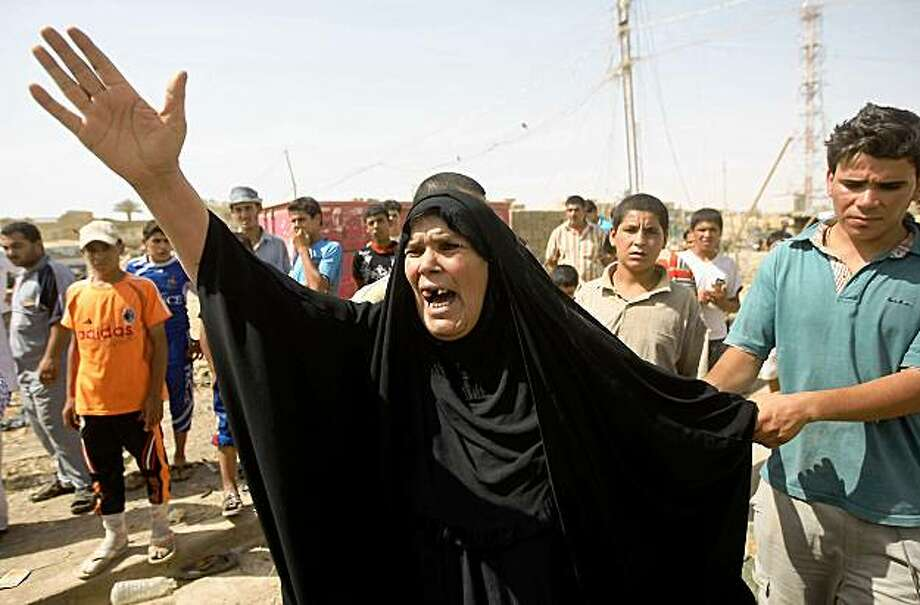 TOPSHOTS An Iraqi woman reacts after learning of her son's death who was killed in a blast outside Al-Shurufi mosque in the northeastern Baghdad district of al-Shaab on July 31, 2009. A string of powerful bomb attacks, targetting Shiite Muslim worshippers as they emerged from mosques across Baghdad, killed 27 people and wounded more than 50, security officials said. TOPSHOTS/AFP PHOTO/AHMAD AL-RUBAYE (Photo credit should read AHMAD AL-RUBAYE/AFP/Getty Images) Photo: Ahmad Al-Rubaye, AFP/Getty Images