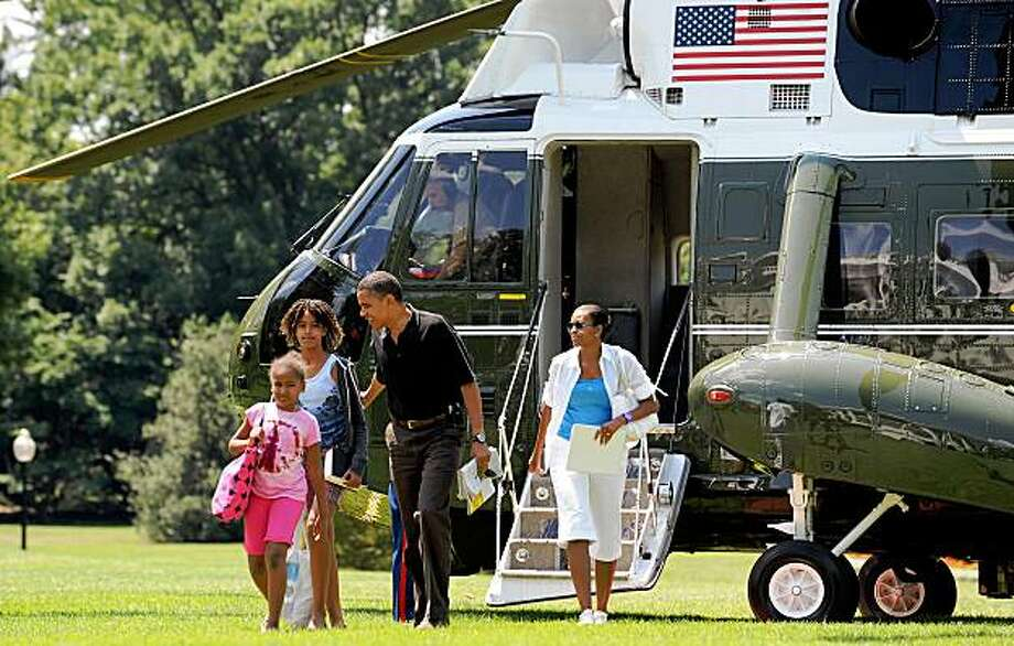 US President Barack Obama, First Lady Michelle Obama (R) and their daughters Malia (2nd-L) and Sasha disembark from Marine One on the South Lawn of the White House in Washington, DC, upon their return from Camp David on July 19, 2009. AFP PHOTO/Jewel SAMAD (Photo credit should read JEWEL SAMAD/AFP/Getty Images) Photo: Jewel Samad, AFP/Getty Images