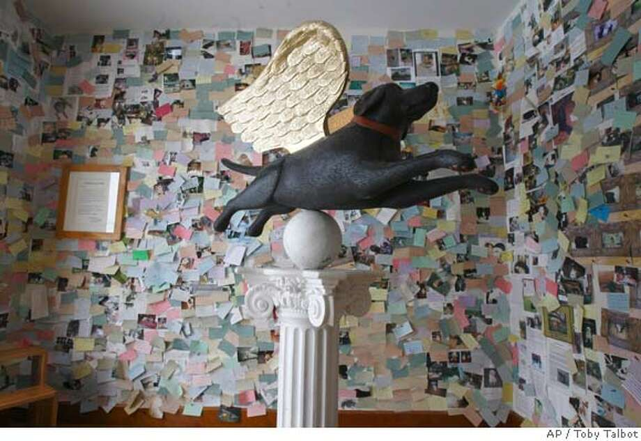** FOR IMMEDIATE RELEASE ** Artie, the angel dog, a black labrador with golden wings, is at the center of the foyer of Stephen Huneck's dog chapel in St. Johnsbury, Vt., Thursday, Dec. 20, 2007. The walls are covered in handwritten remembrances and photographs left by dog owners. (AP Photo/Toby Talbot) Photo: Toby Talbot