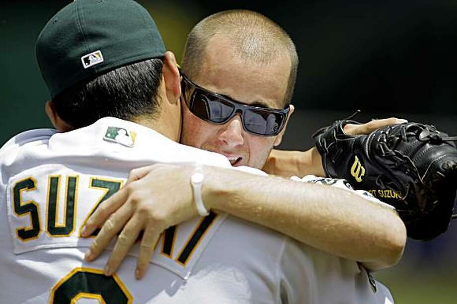Jon Wilhite, right, former Cal State Fullerton baseball star, embraces his former teammate, Oakland Athletics catcher Kurt Suzuki, after throwing out the ceremonial first pitch before a baseball game between the A's and the Los Angeles Angels, Saturday, July 18, 2009, in Oakland, Calif. Wilhite is the sole survivor of the April 9 car crash that killed Angels pitcher Nick Adenhart, Henry Pearson and Courtney Stewart. (AP Photo/Ben Margot) Photo: Ben Margot, AP