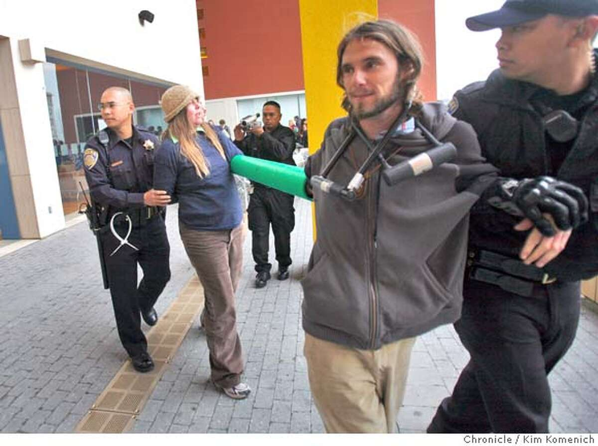 Protesters who used bicycle locks to chain themselves to the east entrance of the William H. Rutter Center at UCSF Mission Bay are detained after being extricated Wednesday, Mar. 19 as participants arrive at other entrances for the U.C. Regents meeting. Photo by Kim Komenich / The San Francisco Chronicle