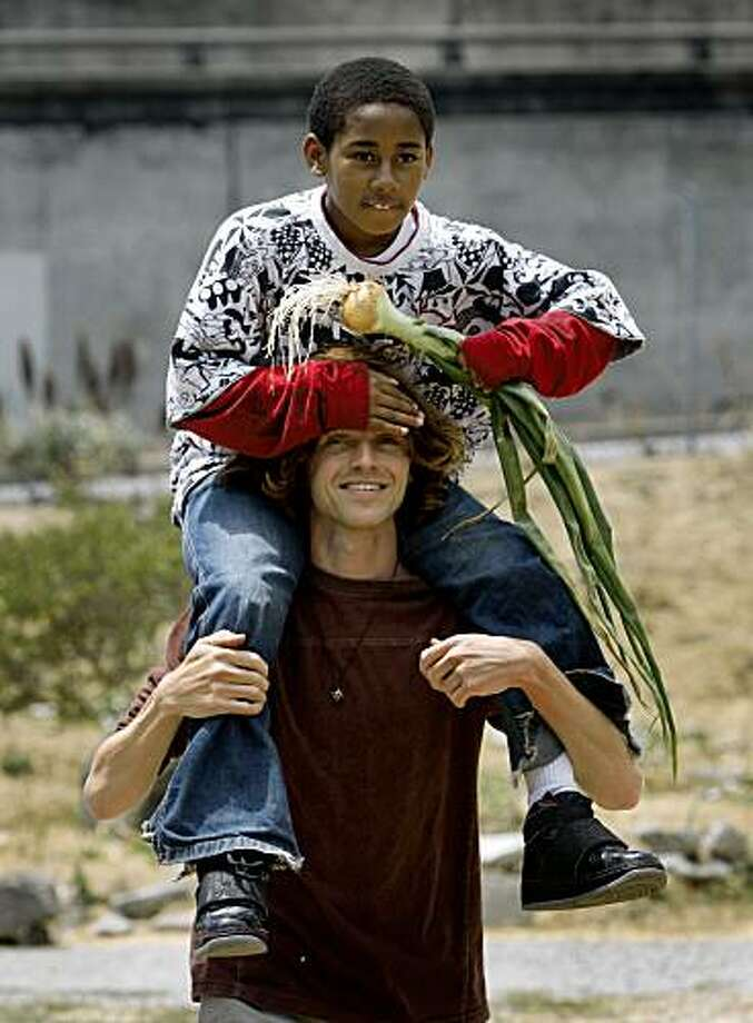 Ryan Geller gives Marquise Brown a lift after the volunteers picked onions and other crops at the Alemany Farms urban garden in San Francisco, Calif., on Thursday, July 16, 2009. The sprawling garden takes up over 4 1/2 acres and is partly on land owned by the city Recreation and Park department and the Housing Authority. Photo: Paul Chinn, The Chronicle