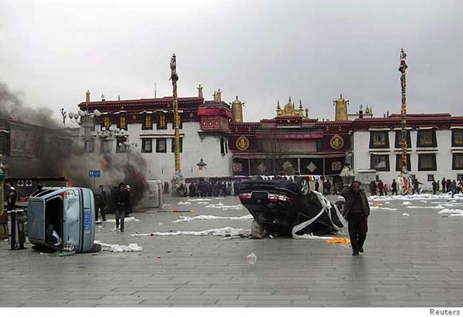 "Residents walk past overturned cars and burning shops in Barkhor Square in front of the 1400-years old Jokhand Temple, a world heritage site, in central Lhasa, Tibet March 14, 2008. Protesters in Tibet's capital burnt shops and vehicles and yelled for independence on Friday as the region was hit by protests, prompting the Dalai Lama to urge Beijing to stop ""brute force"". REUTERS/Stringer (CHINA) Photo: STRINGER/CHINA"