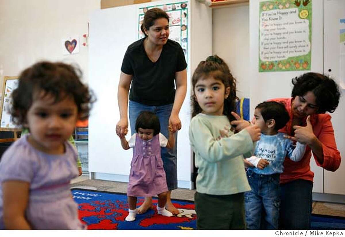 ###Live Caption:Surrounded by other members of the Indian community, Manasi Dharme supports her daughter Jiya Dharne, 2, during a Parents and Me class at the Indian Community Center in Milpitas, Calif. on Thursday, Feb. 28, 2008. Dharne, who used to be a school teacher in India is one of thousands of Indian women, who once had professional jobs in India and who since following their spouses to California where left with restrictive h4 visas that don't allow them to work in the United States. Many of these women have found themselves taking over childcare duties full-time and are forced struggle with issues of boredom and iscolation. Photo by Mike Kepka / San Francisco Chronicle###Caption History:Surrounded by other members of the Indian community, Manasi Dharme supports her daughter Jiya Dharne, 2, during a Parents and Me class at the Indian Community Center in Milpitas, Calif. on Thursday, Feb. 28, 2008. Dharne, who used to be a school teacher in India is one of thousands of Indian women, who once had professional jobs in India and who since following their spouses to California where left with restrictive h4 visas that don't allow them to work in the United States. Many of these women have found themselves taking over childcare duties full-time and are forced struggle with issues of boredom and iscolation. Photo by Mike Kepka / San Francisco Chronicle###Notes:(cq)###Special Instructions:MANDATORY CREDIT FOR PHOTOG AND SAN FRANCISCO CHRONICLE/NO SALES-MAGS OUT