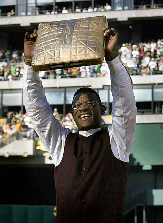 Rickey Henderson holds up a base made of gold as he was honored at the Oakland Coliseum in a pre-game ceremony where his number #24 was retired on August 1, 2009. Photo: Frederic Larson, The Chronicle