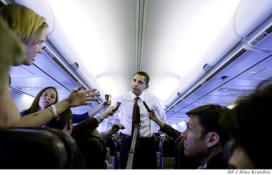 Democratic presidential hopeful Sen. Barack Obama D-Ill., speaks to press on the plane as he headed from Chicago to Washington, Thursday, March 13, 2008.(AP Photo/Alex Brandon) Photo: Alex Brandon