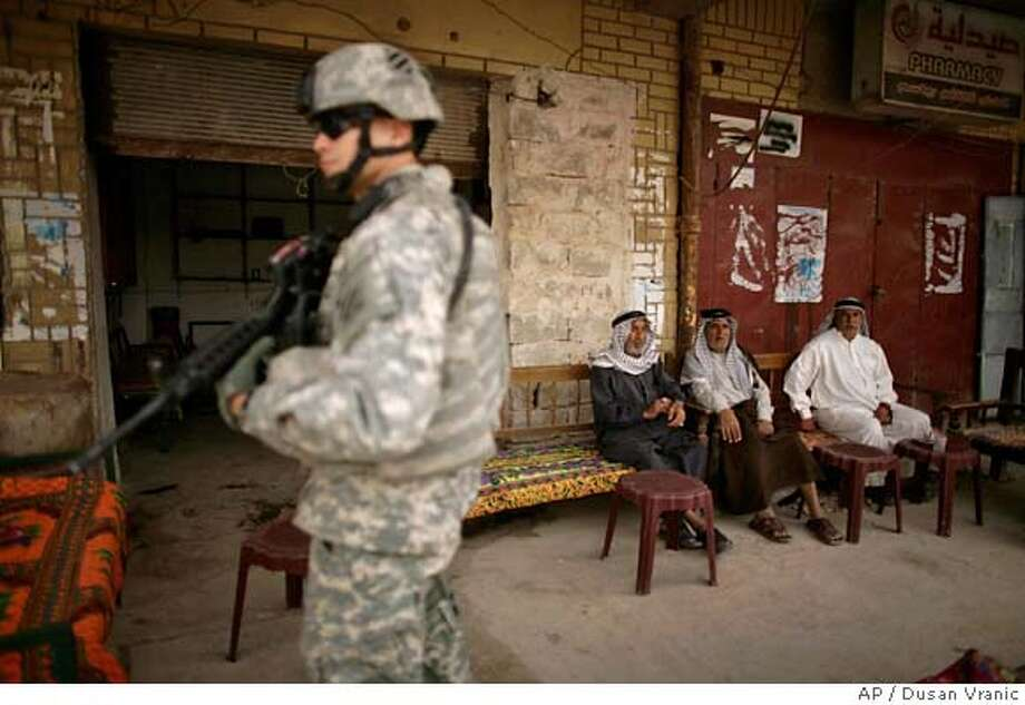 A US soldier is on guard as Iraqis watch Major General Rick Lynch, commander of the Third Infantry Division visits a downtown market in Iskandariyah, 50 kilometers (30 miles) south of Baghdad, Iraq, Saturday, March 15, 2008. (AP photo/Dusan Vranic) Photo: DUSAN VRANIC