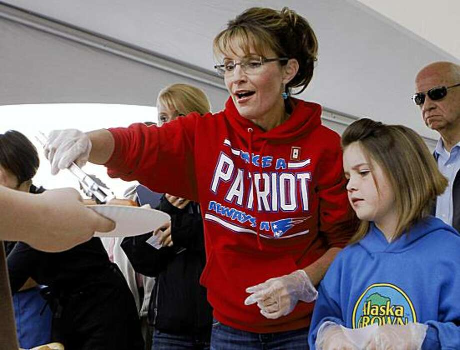 Alaska Gov. Sarah Palin, stands next to her daughter Piper as they dish out hot-dogs during the governor's picnic in Wasilla, Alaska Friday, July 24, 2009.  This is one of three governor's picnics Palin is attending before she resigns as governor in Fairbanks on Sunday, July 26, 2009.  (AP Photo/Al Grillo) Photo: Al Grillo, AP