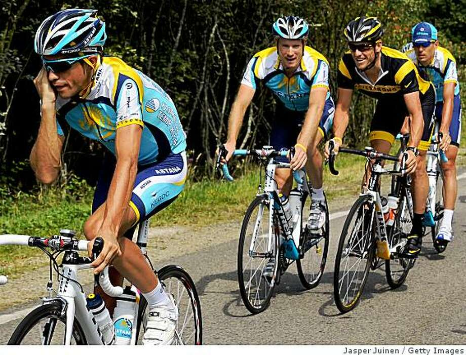 LIMOGES, FRANCE - JULY 13:  Alberto Contador (L) of Spain and team Astana talks on his mobile phone as his teammate Lance Armstrong of USA (2nd R) smiles while talking with Dmitriy Muravyev of Kazakhstann (C) during a training session on the first rest day of the 2009 Tour de France on July 13, 2009 in Limoges, France.  (Photo by Jasper Juinen/Getty Images) Photo: Jasper Juinen, Getty Images