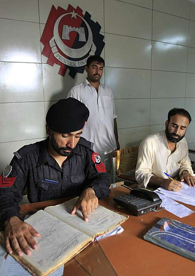 A Pakistani police officer, left, looks at a police record of the  U. S. citizen Daniel Patrick Boyd who was accused of bank robbery dated June 20, 1991, at a local police station in Peshawar, Pakistan on Wednesday, July 29, 2009. Nearly two decades ago, an Islamic court sentenced Daniel Patrick Boyd to lose a hand and foot as punishment for robbing a bank in Pakistan's rough and tumble northwest.An appeals court tossed out the ruling, but the experience did not deter Boyd's Islamic faith _ he now stands accused in the U.S. of plotting to wage holy war.(AP Photo/Mohammad Sajjad) Photo: Mohammad Sajjad, AP