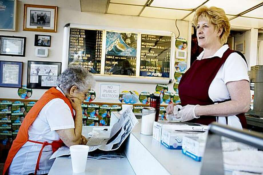 "Lucy Ornellas, cousin of Dolores Larkin, reads the local newspaper while Kari Spencer, who has worked for Caspers for 16 years, watches for customers, in Pleasant Hill, on Monday, July 27, 2009. Spencer says she likes working days because its busier. ""Sometimes the line wraps around the outside."" Second and third generation owners of Caspers, a family-owned business, celebrate their 75th anniversary Tuesday of making hot dogs. Photo: Lianne Milton, Special To The Chronicle"