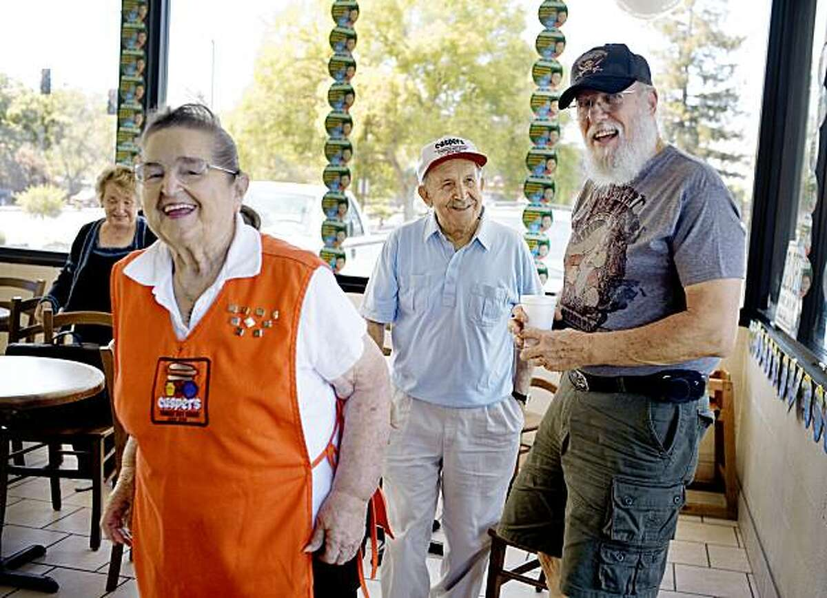Bill Segraves, who owns a gun shop across the street from Caspers, visits with Dolores Larkin and George Rustigian, in Pleasant Hill, on Monday, July 27, 2009. Segraves, a former police officer, used to come in for his morning coffee. Now retired, he comes in to help set up the restaurant everyday since 1998. Second and third generation owners of Caspers, a family-owned business, celebrate their 75th anniversary Tuesday of making hot dogs.