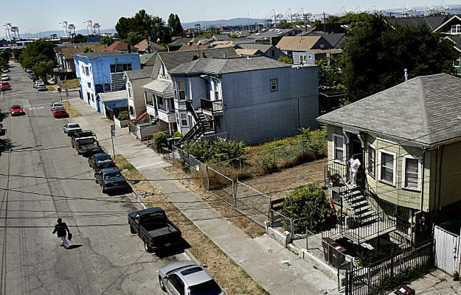 This West Oakland neighborhood near the West Oakland BART station is subject to higher pollution levels because of the proximity of the port, which can be seen in background. State and local air quality officials are funneling $22 million into a program to retrofit the emissions systems on the trucks that move in and out of the Port of Oakland each day. Photo: Brant Ward, The Chronicle