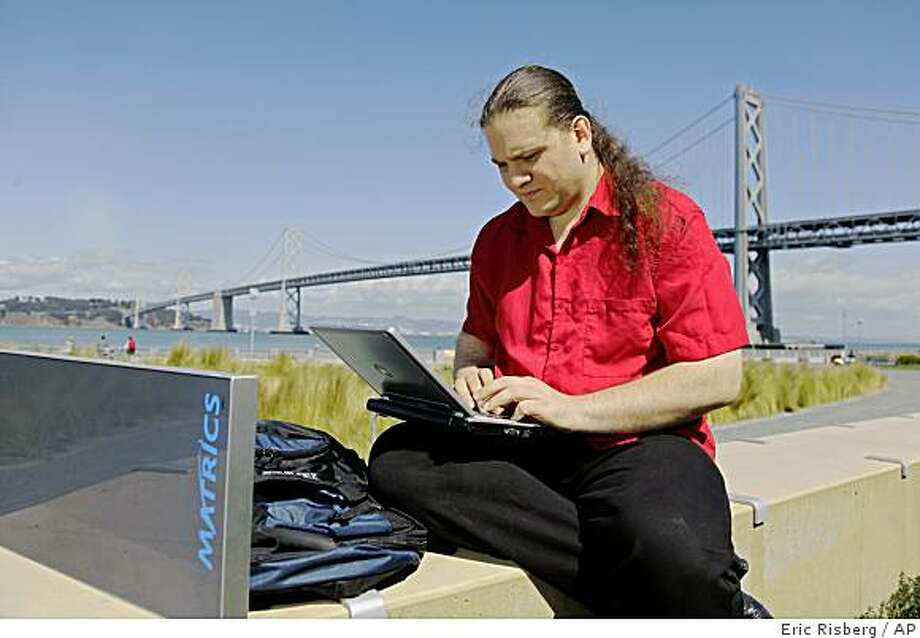 "In this  April 10, 2009. photo, Chris Paget, a self-described ""ethical' hacker,"" sits with his scanning equipment along the Embarcadero in San Francisco seeking information from radio frequency identification, or RFID, chips as people pass by him. In the background is the San Francisco-Oakland Bay Bridge. (AP Photo/Eric Risberg) Photo: Eric Risberg, AP"
