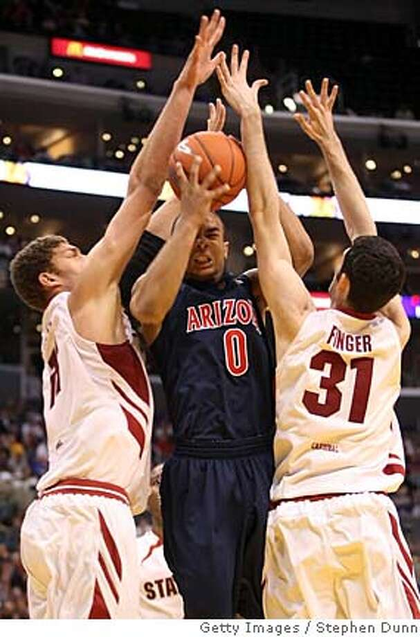 LOS ANGELES, CA - MARCH 13: Jerryd Bayless #0 of the Arizona Wildcats drives to the basket against the defense of Brook Lopez #11 nad Taj Finger #31 of the Stanford Cardinal during the 2008 Pacific Life Pac-10 Men's Basketball Tournament Day Two at Staples Center on March 13, 2008 in Los Angeles, California. (Photo by Stephen Dunn/Getty Images)  Ran on: 03-14-2008  Arizona's Jerryd Bayless finds the going rough against Stanford's Brook Lopez (left) and Taj Finger.  Ran on: 03-14-2008 Ran on: 03-14-2008  Arizona's Jerryd Bayless finds the going rough against Stanford's Brook Lopez (left) and Taj Finger. Photo: Stephen Dunn