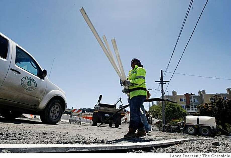Construction worker Carolena Williams from San Francisco removes forms used to hold fresh cement after a new roadway was built into Hunters Point Shipyard that's under going a transformation from a Navy shipyard to a diverse community.  Friday, May 22, 2009. Photo: Lance Iversen, The Chronicle