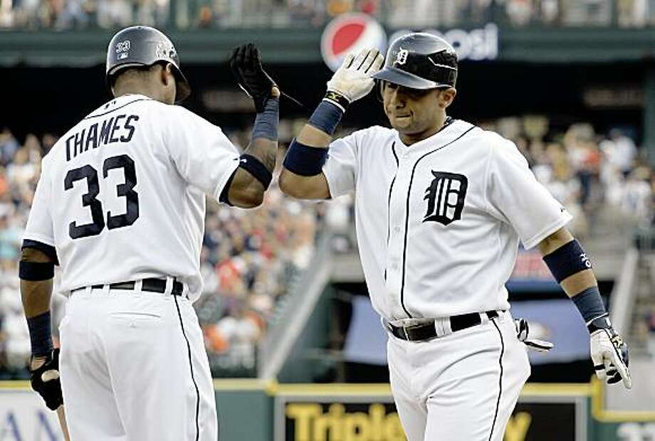 Detroit Tigers' Carlos Guillen, right, is congratulated by Marcus Thames after hitting a solo home run in the second inning of Game 2 of a baseball doubleheader against the Chicago White Sox on Friday, July 24, 2009, in Detroit. (AP Photo/Duane Burleson) Photo: Duane Burleson, AP
