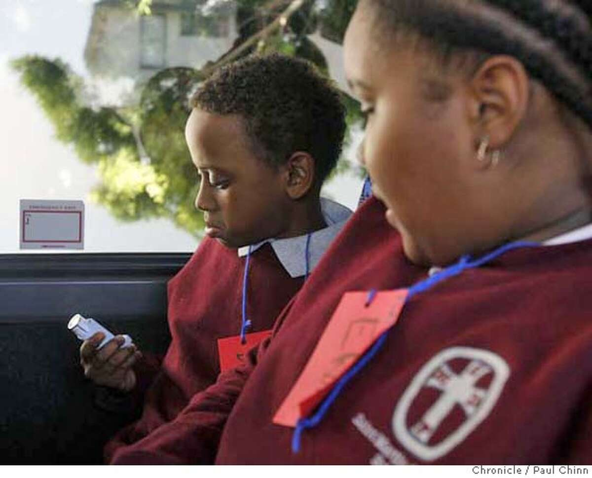 ###Live Caption:Darryl Williams, left, checks his asthma medicine with schoolmate Elaine Barfield before a field trip of the Port of Oakland organized by a coalition of community groups for students from St. Martin de Porres Middle School in Oakland, Calif., on Thursday, Feb. 28, 2008. The trip focused on educating the kids about the rising cases of health problems in the neighborhood, including asthma, caused in large part by pollutants from trucks waiting to pick up cargo at the port. Photo by Paul Chinn / San Francisco Chronicle###Caption History:Darryl Williams, left, checks his asthma medicine with schoolmate Elaine Barfield before a field trip of the Port of Oakland organized by a coalition of community groups for students from St. Martin de Porres Middle School in Oakland, Calif., on Thursday, Feb. 28, 2008. The trip focused on educating the kids about the rising cases of health problems in the neighborhood, including asthma, caused in large part by pollutants from trucks waiting to pick up cargo at the port. Photo by Paul Chinn / San Francisco Chronicle###Notes:Darryl Williams, Elaine Barfield###Special Instructions:MANDATORY CREDIT FOR PHOTOGRAPHER AND S.F. CHRONICLE/NO SALES - MAGS OUT