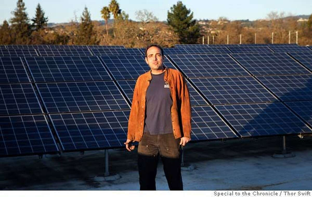 Mark Armstrong stands in front of an array of solar panels on the roof of a program on alternative fuels at Santa Rosa Community College, Monday, Dec. 10, 2007. The program works on various types of alternative fuels for automobiles, from electric to re-used cooking oil. Eventually this array will help power some of the electric cars they are working on. Thor Swift For The San Francisco Chronicle