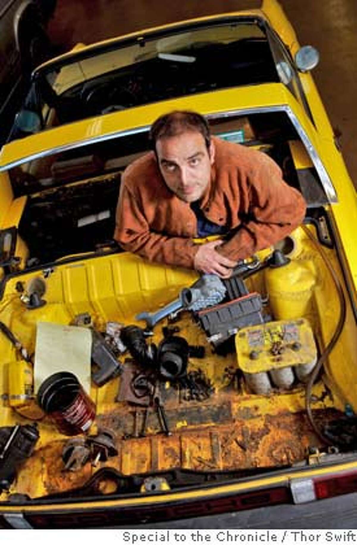 Mark Armstrong stands where the engine normally would go in a car he and his students are converting to a hydraulic-hybrid motor at a program on alternative fuels at Santa Rosa Community College, Monday, Dec. 10, 2007. The program works on various types of alternative fuels for automobiles, from electric to re-used cooking oil. They are hoping this car will get over 100 MPG when the system is working. Thor Swift For The San Francisco Chronicle
