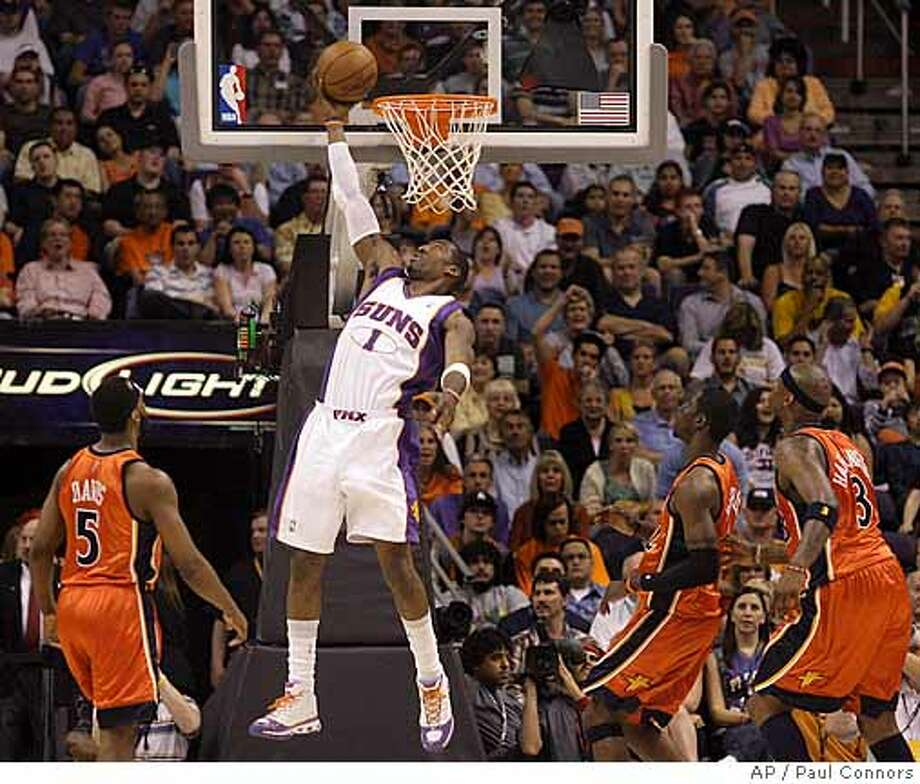 Phoenix Suns forward Amare Stoudemire, center, makes a reverse lay-up as Golden State Warriors players, from left, Baron Davis, Matt Barnes and Al Harrington look on in the first quarter of an NBA basketball game Thursday, March 13, 2008, in Phoenix.(AP Photo/Paul Connors) Photo: Paul Connors