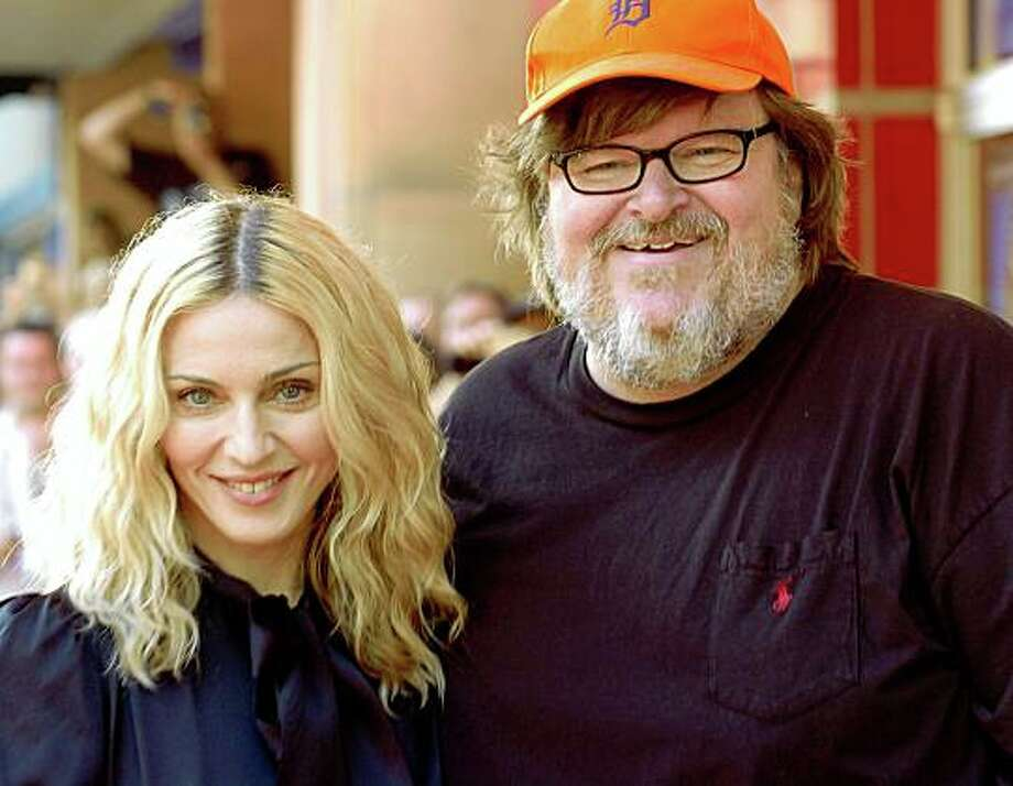 "Madonna poses with filmmaker Michael Moore at the screening of her documentary film ""I Am Because We Are"" at the Traverse City Film Festival, Saturday, Aug. 2, 2008, in Traverse City, Mich.. Moore is a co-founder of the festival, held each summer in Northern Michigan. (AP Photo/John L. Russell) Photo: John L. Russell, AP"