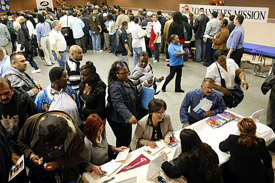 FILE - In this June 4, 2009 file photo, people look for jobs at the Los Angeles Mission Career Fair.  Americans' confidence in the economy darkened further in July as worries about job security offset any enthusiasm about the resumed stock market rally that has helped bolster retirement accounts Tuesday, July 28, 2009.(AP Photo/Damian Dovarganes, file) Photo: Damian Dovarganes, AP