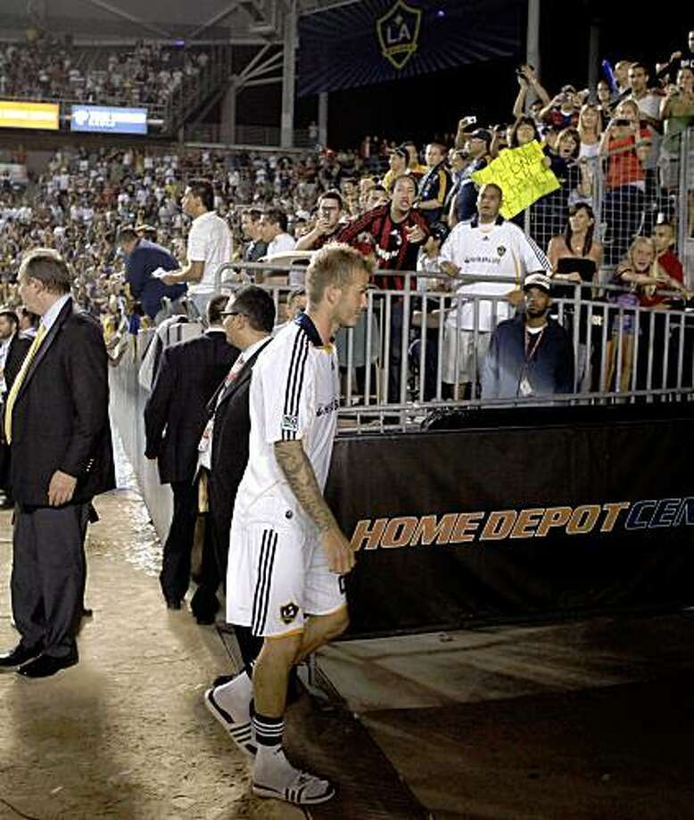 Los Angeles Galaxy's David Beckham leaves the stadium after a friendly soccer game with AC Milan at Home Depot Center in Carson, Calif., Sunday July 19, 2009. Beckham received an ugly reception in his first home game back with the Los Angeles Galaxy, first getting booed then confronting a fan at halftime of his team's 2-2 draw.  (AP Photo/Jae C. Hong) Photo: Jae C. Hong, AP