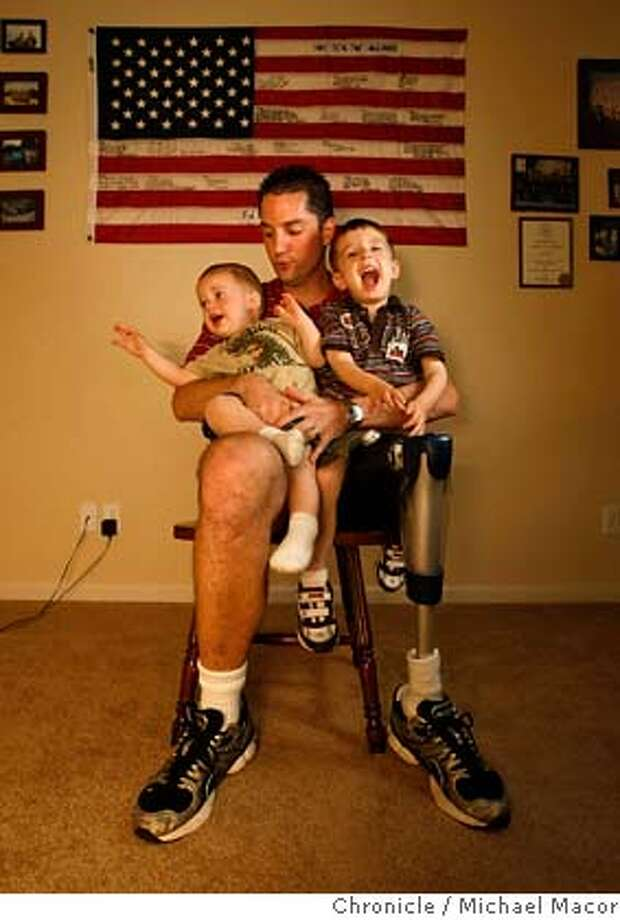 Derek McGinnis with his younger son, Ryan, 1 , and Sean, 3, , at their Waterford, Calif. home, on Mar. 11, 2008. McGinnis, serving as Navy Corpsman, lost his left, to a suicide bomber, back in 2004 during a battle in Fallujah, Iraq. Inside his home office where he keeps memorabilia from his military days with the Navy. Photo by Michael Macor/ San Francisco Chronicle Ran on: 03-16-2008  Derek McGinnis is glad to be alive to watch his sons Ryan and Sean grow after a car bomb cost him his left leg while he served in Fallujah, Iraq. Inside, other Bay Area residents describe the struggles and triumphs they endure as the war in Iraq enters its fifth year. See the profiles on pages 6 and 7. Photo: Michael Macor