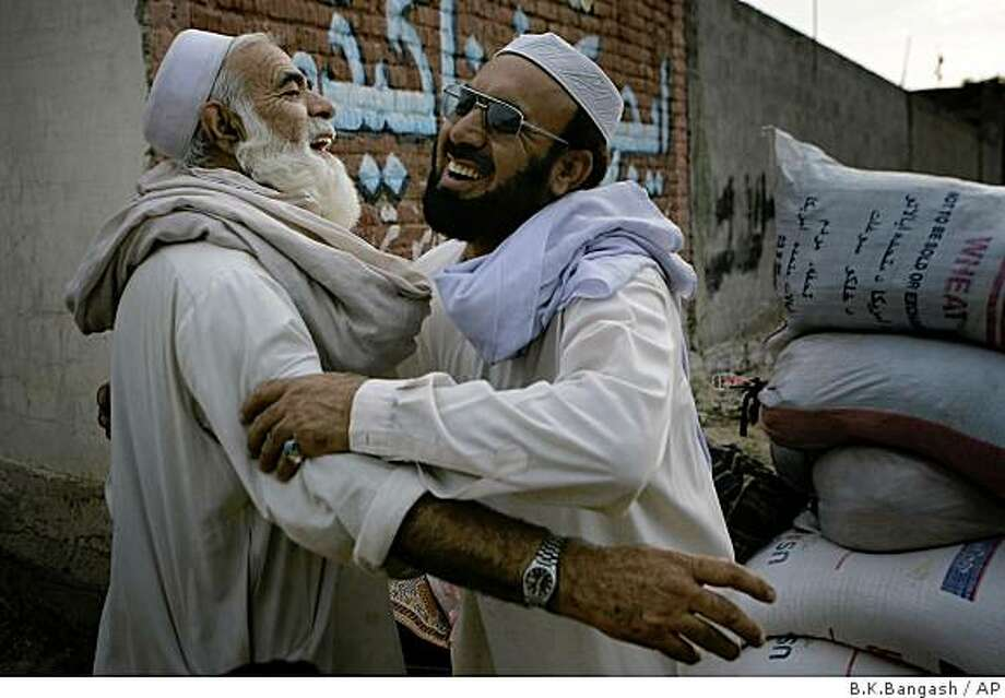 Pakistani displaced resident Khursheed Khan, left, who fled his hometown due to fighting between security forces and Taliban militants, is received by his neighbor upon his arrival in Barikot in Pakistan's troubled Swat Valley  on Monday, July 13, 2009. Pakistan start sending two million refugees to return to their homes in the Swat Valley. (AP Photo/B.K.Bangash) Photo: B.K.Bangash, AP