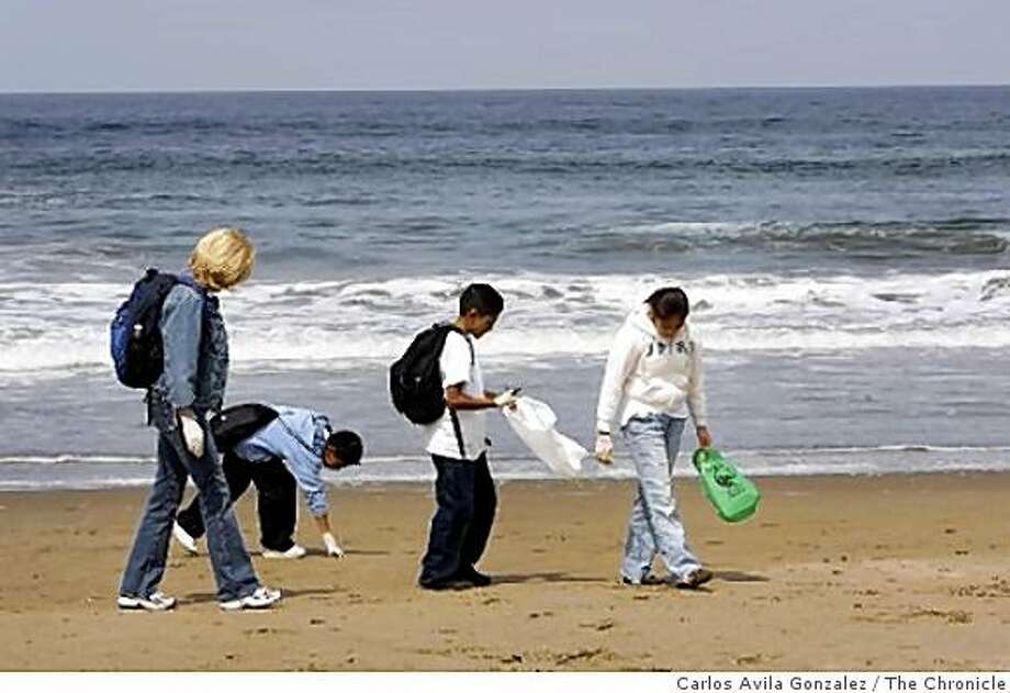 L-R, Maureen Tierney, Jonathan Garcia, in blue, Alex Mendez, in white, and Kleidy Santos, of Bahia Vista School in San Rafael, pick up trash on Ocean Beach as part of Coastal Cleanup Day on Thursday, June 4, 2009. 500 Students from Marin, SF, and Oakland to Clean Ocean Beach for the KidsÕ Ocean Day Adopt-A-Beach Cleanup and Aerial Art Display on Thursday, June 4th, 2009 What: Approximately 500 elementary students will be coming to Ocean Beach for the 16th Annual KidsÕ Ocean Day Adopt-A-Beach Cleanup. Richardson Bay Audubon Center is running the program for the Bay Area region. In addition to the event itself, Audubon staff has led school assembly programs for the students to teach them about the importance of the ocean and how their actions affect it. Photo: Carlos Avila Gonzalez, The Chronicle