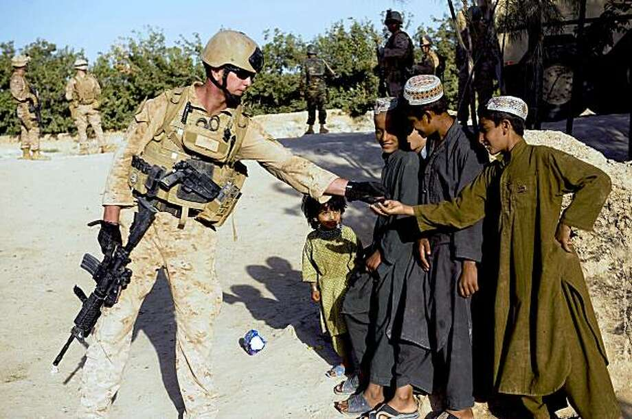 US Marine of 2nd Marine Expeditionary Brigade offers candy to Afghan childern as US Marines help Afghan National Army search compunds for insurgents  in Gharmsir district in Helmand Province on July 27, 2009. About 4,000 US Marines are battling insurgents in a massive offensive launched in the south early this month to clear Taliban militants out of strongholds ahead of presidential and provincial council elections scheduled for August 20.    AFP PHOTO/  Manpreet ROMANA (Photo credit should read MANPREET ROMANA/AFP/Getty Images) Photo: Manpreet Romana, AFP/Getty Images