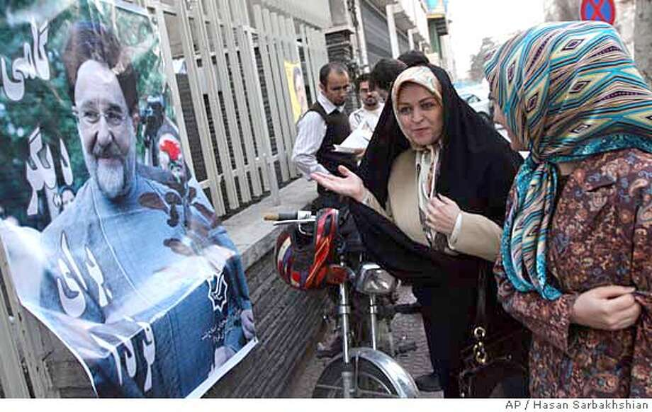 ###Live Caption:Standing next to a photo of former Iranian President Mohammad Khatami, Zahra Eshraghi, granddaughter of Ayatollah Ruhollah Khomeini, founder of Iran's 1979 Islamic revolution, talks to a female in the Youth office of the Coalition of Reformist Groups in Tehran, Iran, in this photo taken on Monday March 10, 2008. Barring prominent reformists from running in Friday's parliamentary elections is a clear evidence of hard-liners seeking to cling to power at the expense of sacrificing democracy, Eshraghi said Tuesday. (AP photo/Hasan Sarbakhshian)###Caption History:Standing next to a photo of former Iranian President Mohammad Khatami, Zahra Eshraghi, granddaughter of Ayatollah Ruhollah Khomeini, founder of Iran's 1979 Islamic revolution, talks to a female in the Youth office of the Coalition of Reformist Groups in Tehran, Iran, in this photo taken on Monday March 10, 2008. Barring prominent reformists from running in Friday's parliamentary elections is a clear evidence of hard-liners seeking to cling to power at the expense of sacrificing democracy, Eshraghi said Tuesday. (AP photo/Hasan Sarbakhshian)###Notes:Zahra Eshraghi###Special Instructions:PHOTO TAKEN MONDAY, MARCH 10, 2008 Photo: Hasan Sarbakhshian