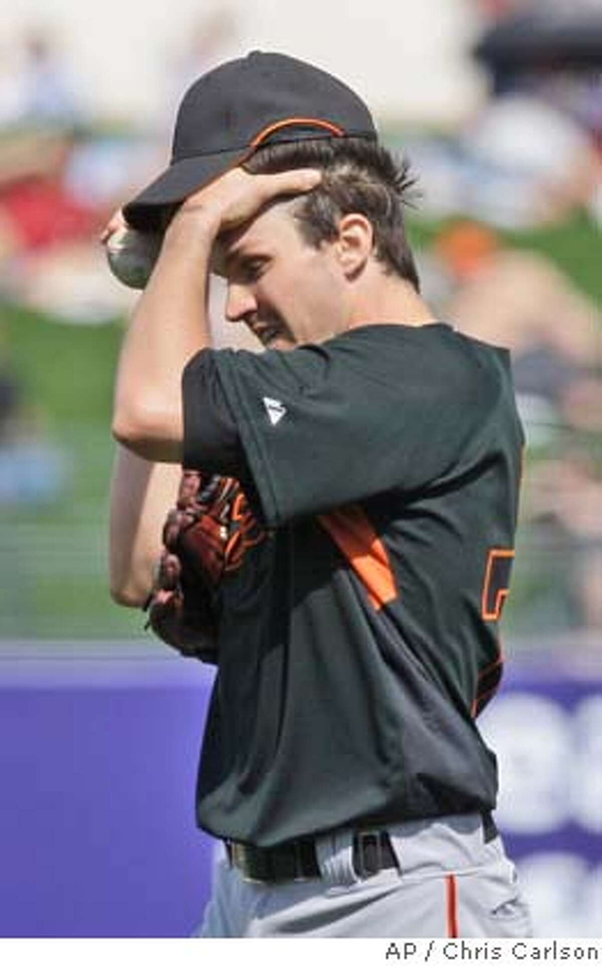 San Francisco Giants pitcher Barry Zito wipes his face after giving up his third run to the Kansas City Royals in the third inning during a spring training baseball game in Surprise, Ariz., Monday, March 10, 2008. (AP Photo/Chris Carlson)