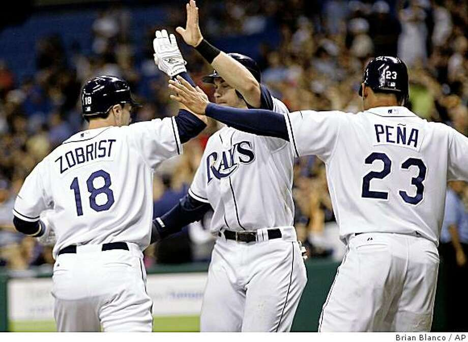 Tampa Bay Rays' Ben Zobrist, Evan Longoria and Carlos Pena, from left, celebrate at the plate after Zobrist's three-run home run in the fourth inning of a baseball game against the Toronto Blue Jays on Wednesday, July 8, 2009, in St. Petersburg, Fla. (AP Photo/Brian Blanco) Photo: Brian Blanco, AP