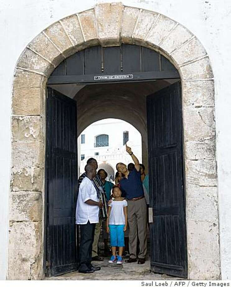 "US President Barack Obama (R), alongside his daughter Sasha (C), points up while standing in ""the Door of No Return"" during a tour of Cape Coast Castle, a former slavery outpost, in Cape Coast, Ghana, on July 11, 2009. The visit marks Obama's first visit to subsaharan Africa as President. Photo: Saul Loeb, AFP / Getty Images"