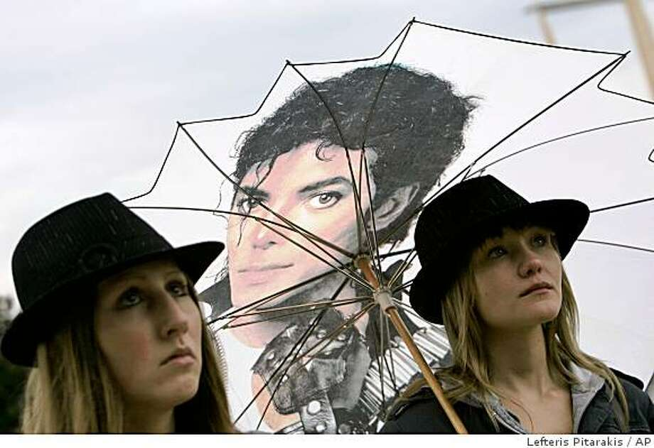 This July 7, 2009 file photo shows Michael Jackson fans watching his memorial broadcast live from Los Angeles on a TV screen outside the O2 arena in southeast London where he was scheduled to play 50 shows from July 2009. (AP Photo/Lefteris Pitarakis,File) Photo: Lefteris Pitarakis, AP
