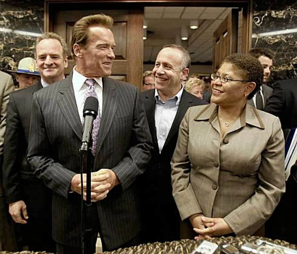 Gov. Arnold Schwarzenegger, front left, smiles at Senate President Pro Tem Darrell Steinberg, D-Sacramento, second from right and Assembly Speaker Karen Bass, D-Los Angeles, after emerging from his office to announce an agreement has been reached to solve California's budget problem, at the Capitol in Sacramento, Calif., Monday, July 20, 2009. Schwarzenegger met with Steinberg, Bass and Republican Leaders. Assembly Minority Leader Sam Blakeslee, R-San Luis Obispo, left, and Senate Minority Leader Dennis Hollingsworth, of Temecula, unseen, most of the day to hammer a an agreement to close the state's $26.3 billion budget deficit.(AP Photo/Rich Pedroncelli)