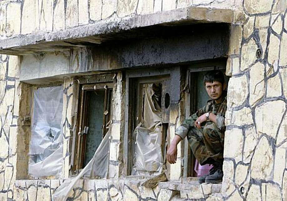 An Afghan soldier watches the street from a window ledge following suicide attacks in Gardez, the provincial capital of Paktiya province east of Kabul, Afghanistan on Tuesday, July 21, 2009. Militants attacked several government centers in an eastern Afghan city Tuesday in a complex attack that has become a signature of major Taliban assaults. Police shot and killed two militant suicide bombers hiding under women's burqas, officials said. (AP Photo/Musadeq Sadeq) Photo: Musadeq Sadeq, AP