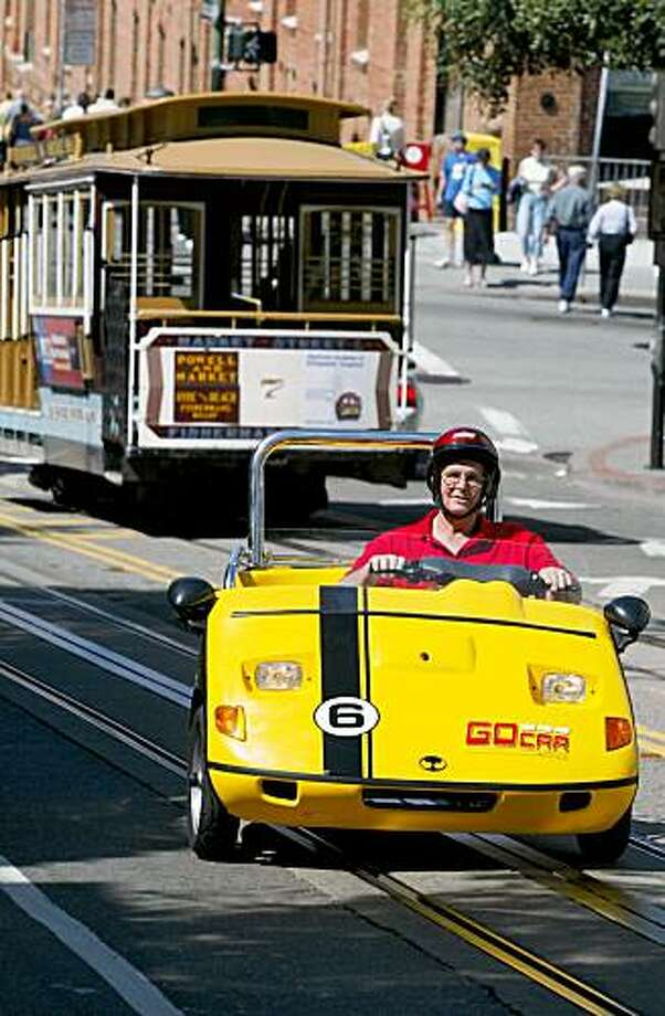 Tom Ruddick of Muncie, Indiana, drives up Hyde Street in a GoCar motorized cart, one of eight that have become big hits with tourists and San Francisco natives alike. The new SF company called GoCar Rentals is renting two-seat moped cars equipped with a Global Positioning System giving tourists an automated talking guided tour of SF. The company uses a Trigger Scooter Car, a bright yellow three-wheeled vehicle that looks like a golf cart  Photo taken on 04/29/04 in San Francisco, Ca. Photo: Carlos Avila Gonzalez, The Chronicle