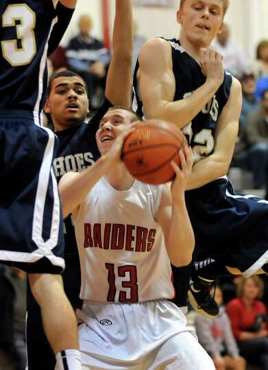 Mechanicville's Jordan McBride (13) fights his way to the hoop against Cohoes' defense during their