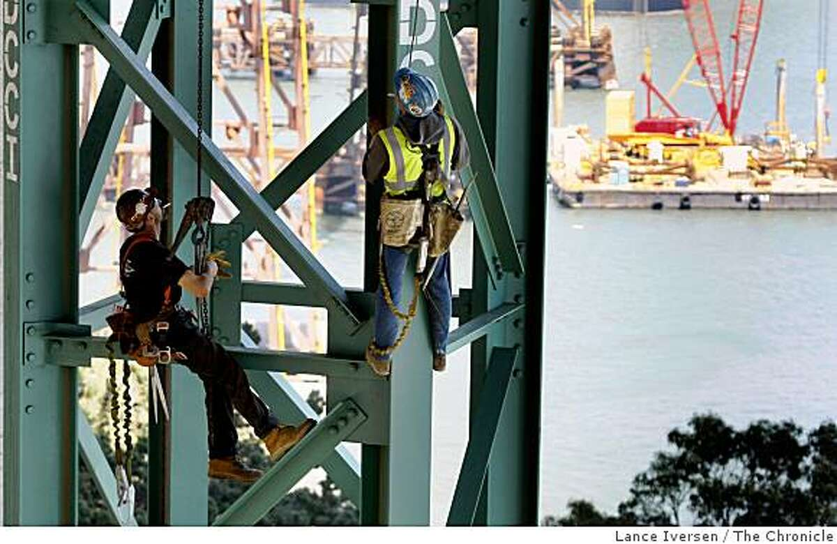 Two ironworkers from San Francisco take a smoke break as they remove a temporary support pier that once held up the Bay Bridge detour Tie-In. A 300-foot double-desk section of the Bay Bridge east of Yerba Buena Island Tunnel will be cut and slid away on Labor Day weekend. The new temporary replacement will be slid into place allowing for the removal of the old span. The new detour will be a slightly different drive, as the roadway curves to the south, requiring drivers to slow down while approaching or leaving the tunnel. Wednesday July 1, 2009.