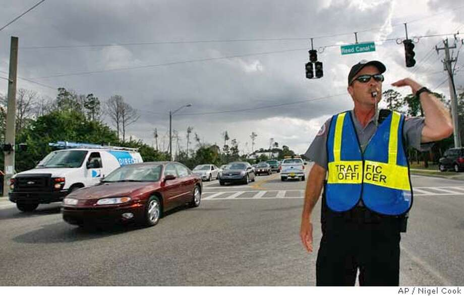 Port Orange Community Service officer, Tom Wilson, directs traffic along Clyde Morris and Reed Canal in Port Orange, Fla., as a statewide power outage knocked out power to traffic lights slowing traffic at some intersections around the city, Tuesday, Feb. 26, 2008. (AP Photo/Daytona Beach News-Journal, Nigel Cook) Photo: NIGEL COOK