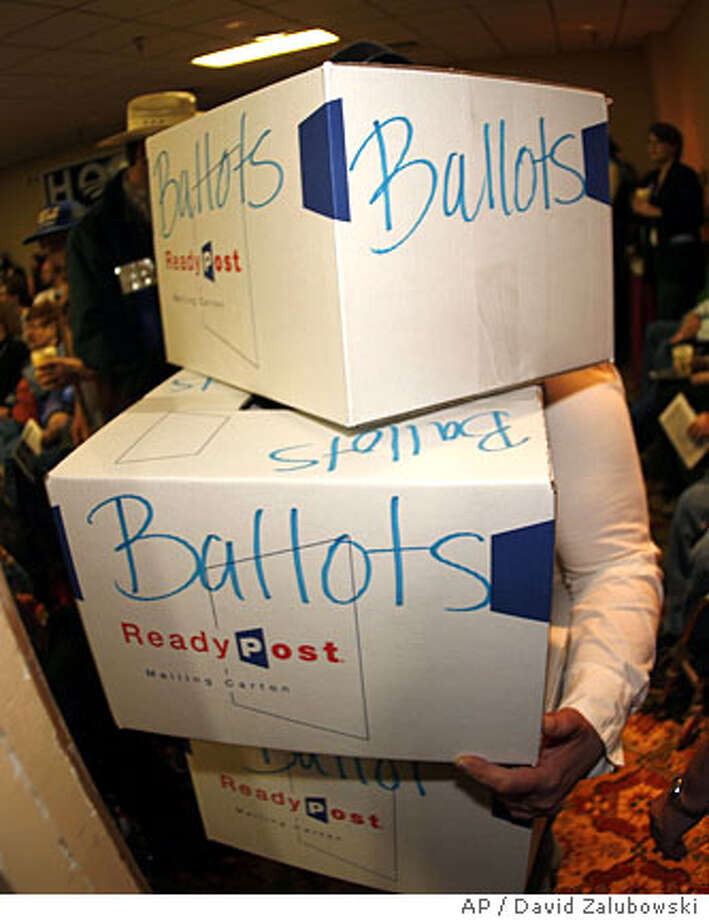 LeAnne Miller carries boxes in for collecting ballots at the Wyoming Democratic caucuses in Casper, Wyo., early on Saturday, March 8, 2008. (AP Photo/David Zalubowski) Photo: David Zalubowski