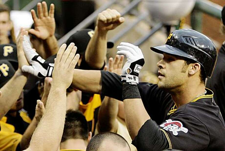 Pittsburgh Pirates' Garrett Jones, right, celebrates with teammates in the dugout after hitting a  first-inning solo-homer off San Francisco Giants pitcher Tim Lincecum during a baseball game in Pittsburgh Friday, July 17, 2009.(AP Photo/Gene J. Puskar) Photo: Gene J. Puskar, AP
